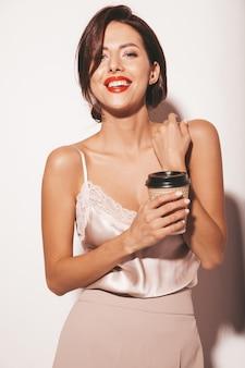 아름 다운 관능적 인 갈색 머리 여자의 초상화입니다. 우아한 베이지 클래식 옷과 넓은 바지에 소녀. 플라스틱 커피 컵을 들고 모델