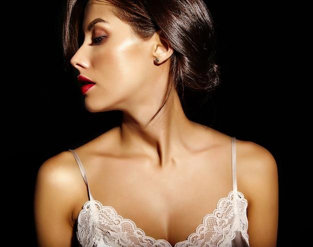 Портрет красивой чувственной милой сексуальной брюнетки женщины с красными губами в пижамном белье на черном фоне