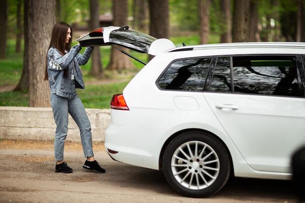 Портрет красивой сексуальной модели женщины брюнетки в джинсовой куртке, стоящей около белого автомобиля и открывающей хэтчбек. концепция моды идея для фотосессии девушки с автомобилем. горизонтальный.