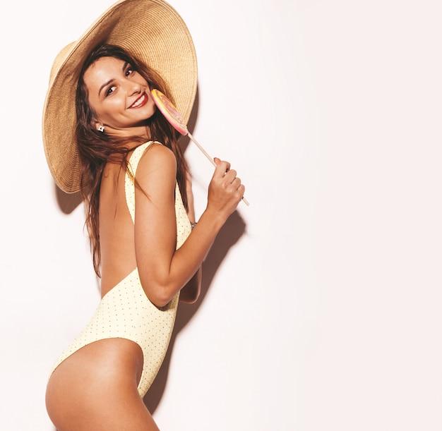 美しいセクシーな笑顔ブルネットの女性の肖像画。カジュアルな夏の黄色のボディランジェリーと大きな帽子に身を包んだ女の子。分離モデルと食べるロリポップ
