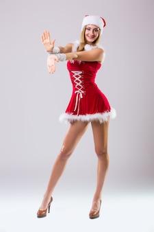 Портрет красивой сексуальной женщины, носящей, как танец санта-клауса, изолированного на белом фоне