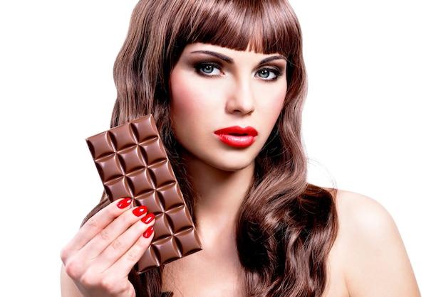チョコレートのバーと美しいセクシーな女性の肖像画。白で隔離の明るい化粧とクローズアップの顔。
