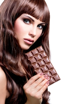 チョコレートのバーを持つ美しいセクシーな女性の肖像画-白で隔離。