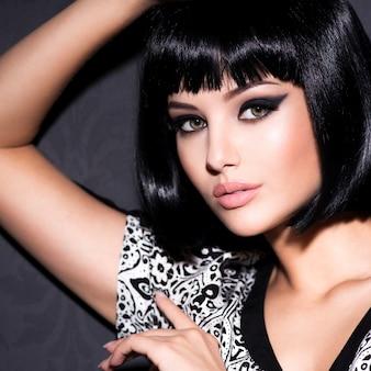 Портрет красивой сексуальной женщины с ярким макияжем, позирующей на сером фоне