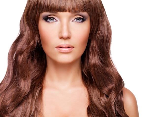 長い赤い髪の美しいセクシーな女性の肖像画。白で隔離の巻き毛の髪型のクローズアップの顔。
