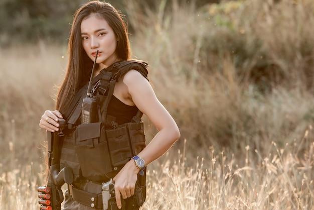 射撃コンピュータゲームesportsswat戦闘機でショットガンとピストルを持つ美しいセクシーな女性の肖像画