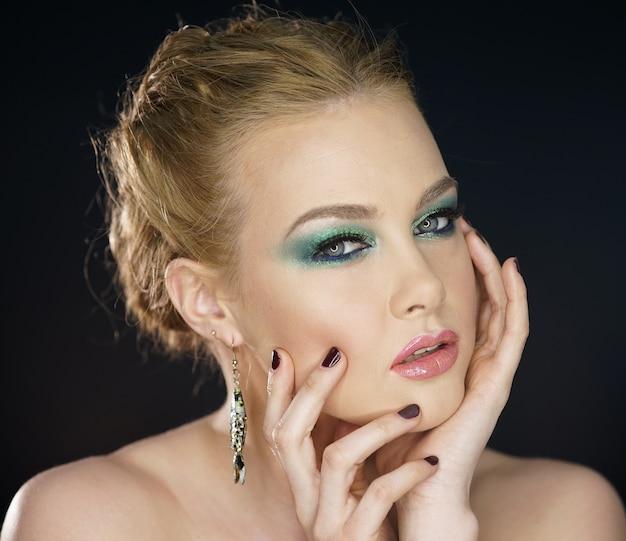 Портрет красивой сексуальной молодой девушки с идеальным макияжем для лица, мягкой свежей здоровой кожей и густыми длинными черными ресницами.