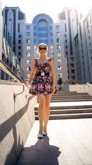 Портрет красивой сексуальной молодой женщины в коротком платье и солнцезащитных очках позирует на каменной лестнице в солнечных лучах