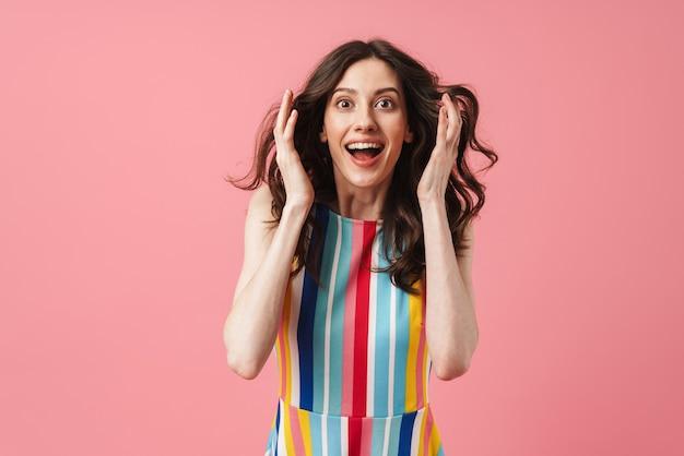 Портрет красивой потрясенной удивленной позитивной милой женщины, позирующей изолированно над розовой стеной