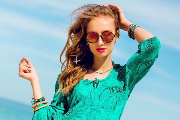 Портрет красивой стройной загорелой женщины с прекрасным предзнаменованием в ярком пляжном платье в стиле бохо и крутых аксессуарах