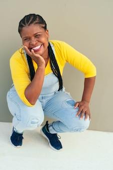 壁にもたれて美しい笑顔のアフリカの女性の肖像画