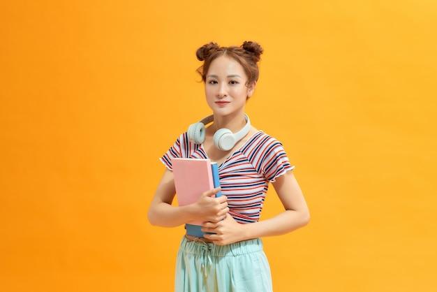 美しい笑顔のアジアの女性の肖像画。黄色の背景に若い学生