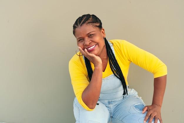 壁にもたれて美しい笑顔の黒人女性の肖像画