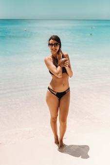 Портрет красивого усмехаясь брюнет в купальнике стоя на пляже и выпивая коктеиле.