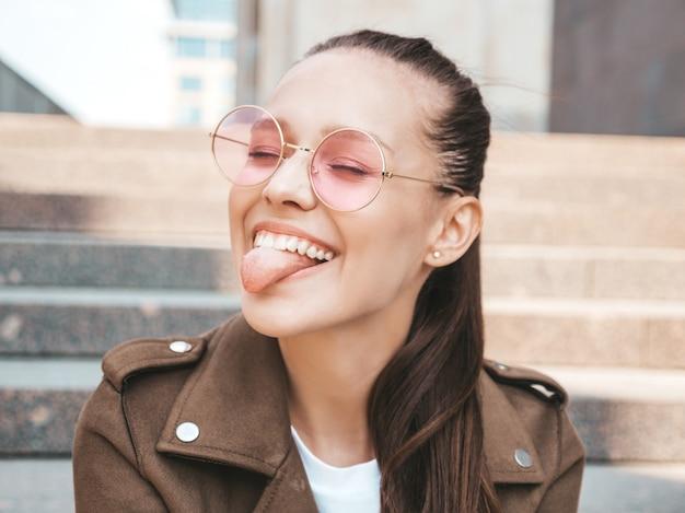 Портрет красивой улыбчивой брюнетки, одетой в летнюю одежду в стиле хипстерской куртки, показывающей ее язык
