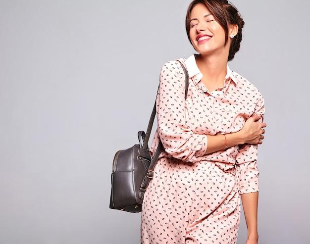 Портрет красивой улыбающейся милой модели брюнетки в повседневной летней одежде без макияжа на серой стене с ручкой