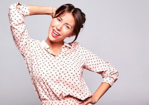 Портрет красивой улыбающейся милой брюнетки модели женщины в повседневной летней одежде без макияжа, изолированной на серой стене