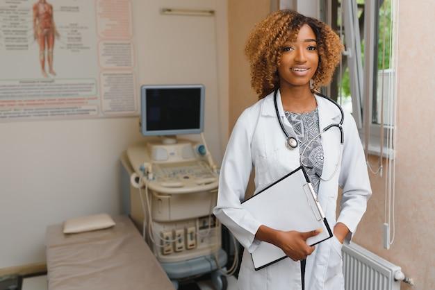 Портрет красивой улыбающейся женщины-афро-американского доктора, стоящей в медицинском кабинете