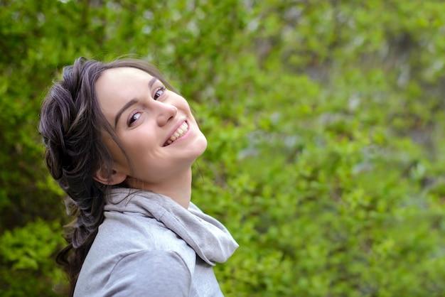 Портрет красивой улыбающейся девушки кареглазой шатенки в светло-сером пиджаке на фоне зеленой листвы