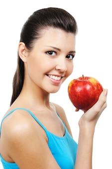 Портрет красивой улыбающейся девушки, едящей яблоко - изолированные