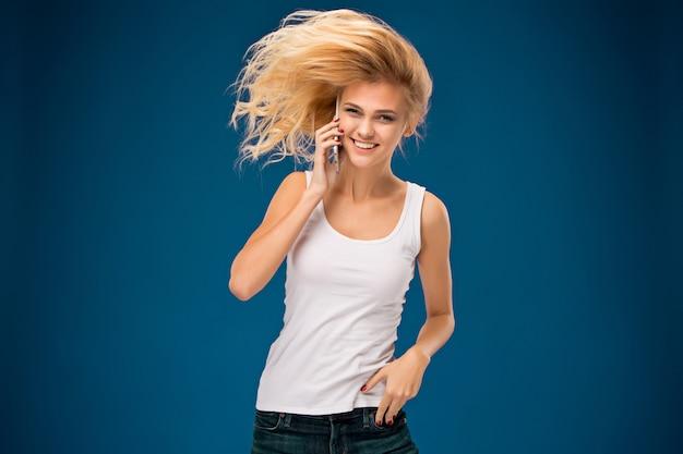 彼女の手に電話でモダンな美しい笑顔の少女の肖像画