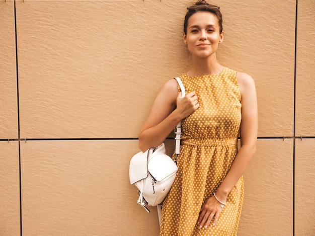 여름 노란 드레스를 입고 아름 다운 웃는 hipster 모델의 초상화. 거리에서 포즈 유행 소녀입니다. 재미 있고 긍정적 인 여자 재미