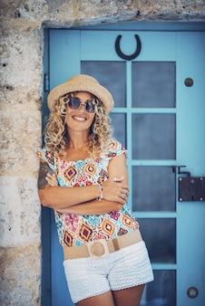 閉じたドアの前で腕を組んで壁にもたれてサングラスと麦わら帽子の美しい笑顔の流行に敏感な若い女性の肖像画。腕を組んでポーズをとっているかなり入れ墨の女性。