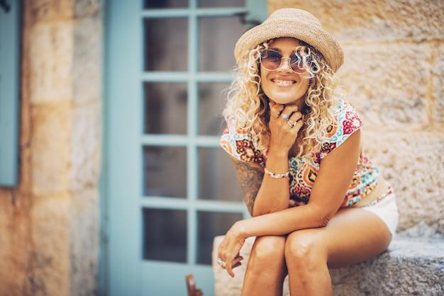 明るい晴れた日に屋外に座っているサングラスと麦わら帽子の美しい笑顔の流行に敏感な若い女性の肖像画。余暇を過ごす良い気分でスタイリッシュな入れ墨の女性