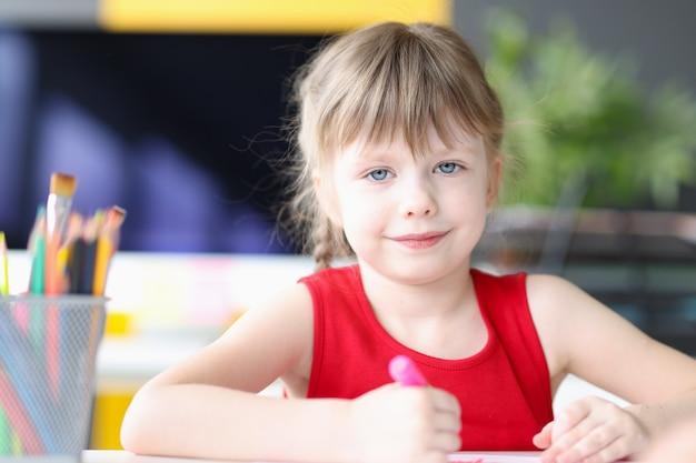 연필로 그림을 그리는 아름다운 미소 짓는 어린 소녀의 초상화 미세 운동 기술 개발