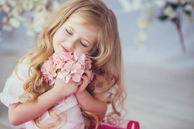 Портрет красивой улыбающейся маленькой девочки в красивом платье, сидящей на светлом деревянном полу