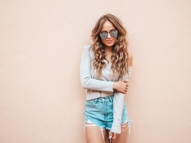 Портрет красивой улыбающейся модели, одетой в летние хипстерские джинсы, шорты, одежда