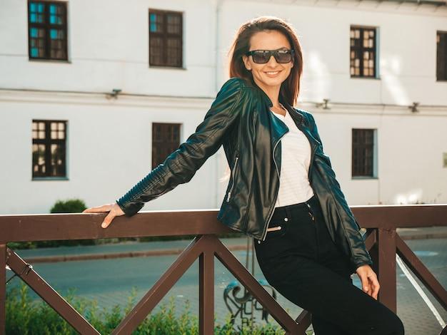Портрет красивой улыбающейся модели. девушка одета в летнюю битник черную кожаную куртку и джинсы. модная женщина позирует на улице