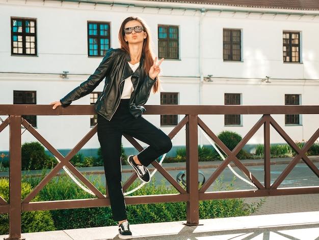 美しい笑顔のモデルの肖像画。夏の流行に敏感な黒い革のジャケットとジーンズに身を包んだ女性。通りでポーズをとるトレンディな女性