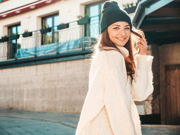 美しい笑顔のモデルの肖像画。暖かいヒップスターの白いセーターとビーニーに身を包んだ女性。通りでポーズをとる