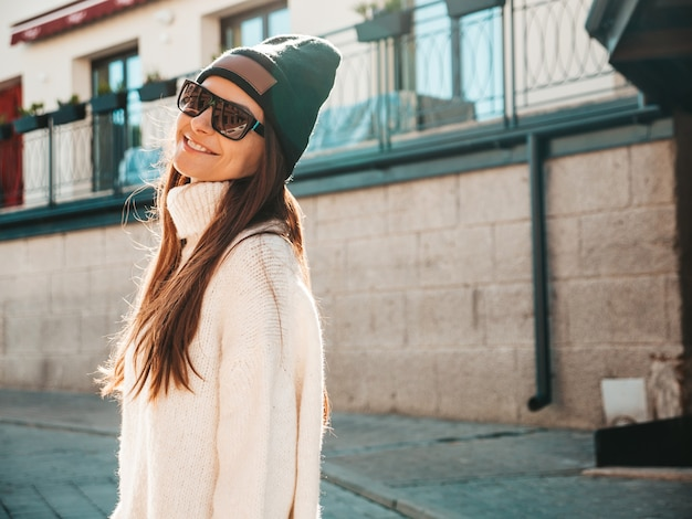美しい笑顔のモデルの肖像画。暖かいヒップスターの白いセーターとビーニーに身を包んだ女性。通りでポーズをとるトレンディな女の子