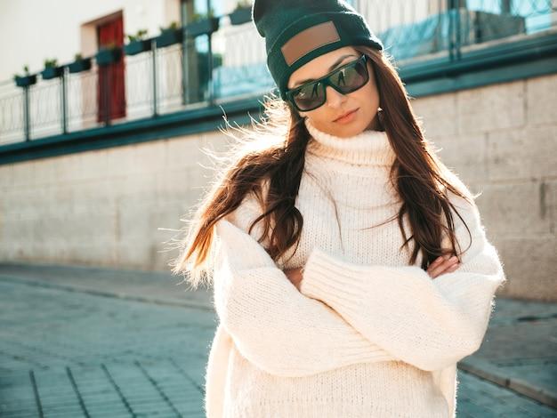 美しい笑顔のモデルの肖像画。暖かいヒップスターの白いセーターとビーニーに身を包んだ女性。通りでポーズをとるトレンディな女性