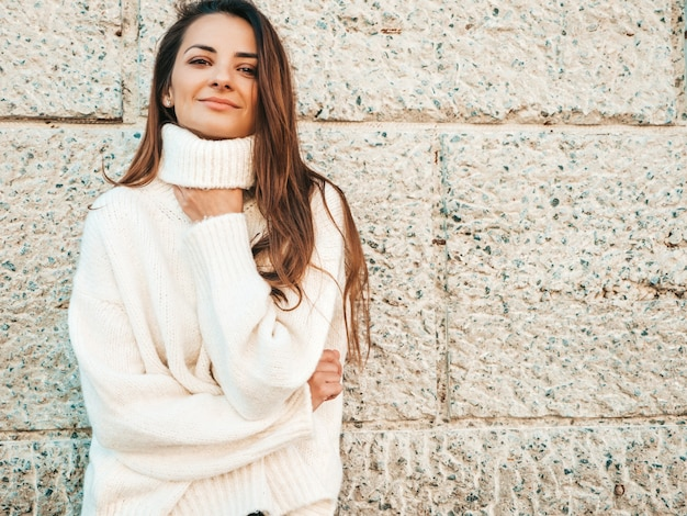 美しい笑顔のモデルの肖像画。暖かいヒップスターの白いセーターを着た女性。通りの壁の近くでポーズをとる
