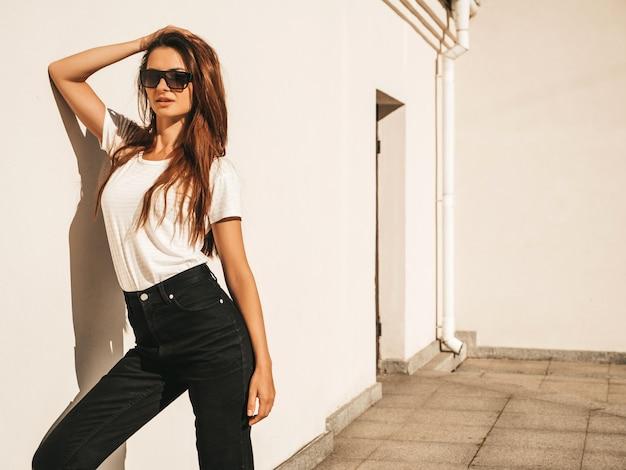 サングラスで美しい笑顔のモデルの肖像画。夏の流行に敏感な白いtシャツとジーンズに身を包んだ女性。通りの壁の近くでポーズをとる