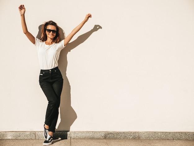Портрет красивой улыбающейся модели в солнечных очках. девушка, одетая в летнюю хипстерскую белую футболку и джинсы. позирует возле стены на улице