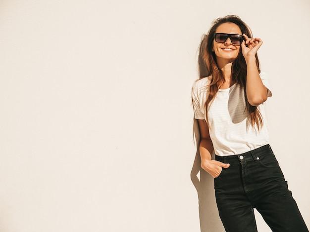 サングラスで美しい笑顔のモデルの肖像画。夏の流行に敏感な白いtシャツとジーンズに身を包んだ女性。通りの壁の近くでポーズをとるトレンディな女の子