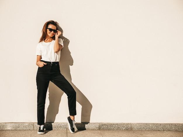 Портрет красивой улыбающейся модели в солнечных очках. девушка одета в летнюю хипстерскую белую футболку и джинсы. модная девушка позирует возле стены на улице