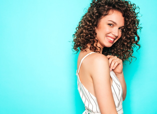 아프리카와 아름 다운 미소 모델의 초상화는 여름 hipster 옷을 입고 헤어 스타일을 곱슬 머리. 파란색 벽 근처 포즈 섹시 평온한 소녀.