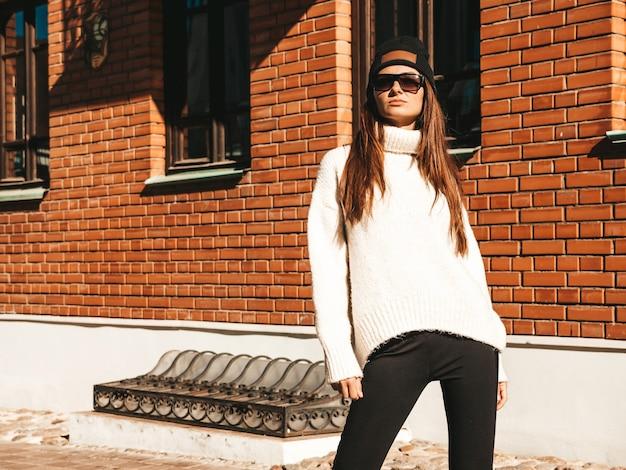 美しい笑顔のモデルの肖像画。暖かいヒップスターの白いセーターとビーニーに身を包んだ女性。彼女は通りでポーズをとる