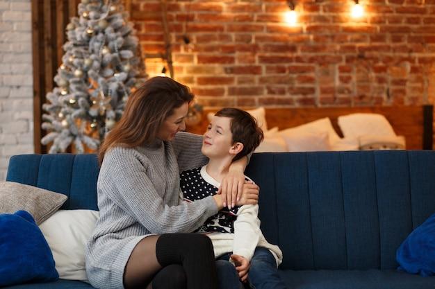 Портрет красивой улыбающейся матери и сына, обнимающихся в канун рождества