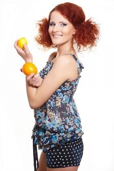 Портрет красивой улыбающейся рыжей рыжей женщины в летнем платье на белом с апельсином и лимоном