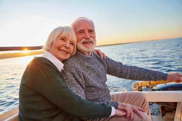 一緒に抱き締めてリラックスしながら手をつないで美しい笑顔の年配のカップルの肖像画