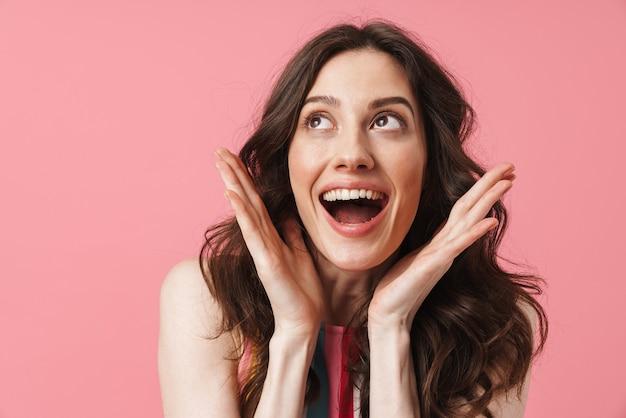 Портрет красивой улыбающейся удивленной позитивной милой женщины, позирующей изолированно над розовой стеной