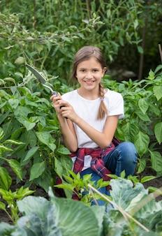 정원에서 일하고 아름 다운 미소 십 대 소녀의 초상화