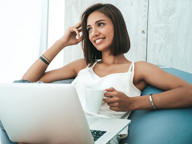 흰색 잠옷을 입은 아름다운 웃는 여성의 초상화. 부드러운 가방 의자에 앉아 노트북을 사용하는 평온한 모델.