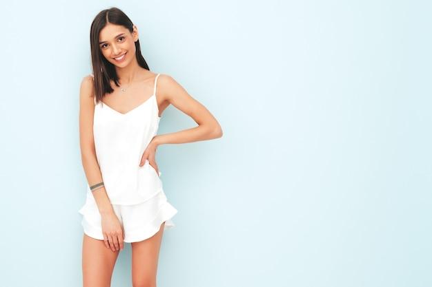 Портрет красивой улыбающейся женщины, одетой в белую пижаму.